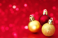 Christmas balls on red defocused lights background. Stock Image