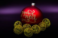 Christmas balls red and gold. `Joyeux Noël`, `Happy Christmas`, Red and gold Christmas balls on a purple background Royalty Free Stock Photography