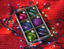 Christmas balls on red knitted background royalty free stock photos