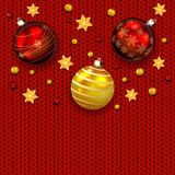 Christmas balls on red knitted pattern Royalty Free Stock Photography