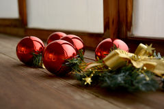 Christmas balls. Red christmas balls with reflection, gold ribbon bow and green branch on wooden table Royalty Free Stock Photo