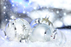 Christmas balls and reflective background. Silver christmas ornamnets in snow before reflective background Royalty Free Stock Image