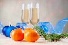Christmas balls, ribbon, fir tree branch, mandarins and champagne Stock Photos
