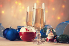 Christmas balls, ribbon, snow globes and champagne. On a table Royalty Free Stock Images