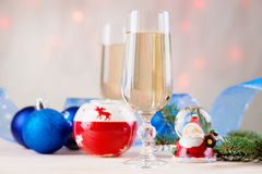 Christmas balls, ribbon, snow globes and champagne. On a table Royalty Free Stock Photography