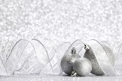 Christmas balls and ribbons. Decoration on shiny silver background royalty free stock images