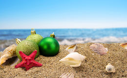 Christmas balls on sand with sea in background. Christmas balls and shells on sand with summer sea background Royalty Free Stock Images