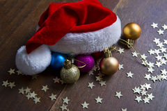 Christmas balls and Santa hat on wood background Stock Photos