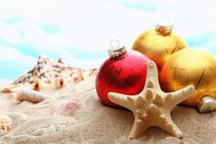 Christmas balls and seashells on the beach Stock Image