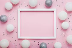 Christmas balls, sequins and picture frame on stylish pink table top view. Fashion background. Flat lay. Party mockup.