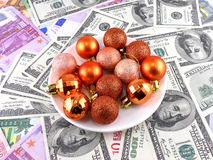 Christmas balls set on white plate, dollar background Royalty Free Stock Photo
