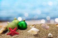 Christmas balls and shells on the beach. Christmas balls and shells on sand with summer sea background Royalty Free Stock Image