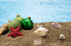 Christmas balls and shells on sand. With summer sea background Stock Image