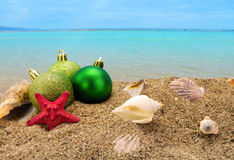 Christmas balls and shells on sand with summer sea. Background Royalty Free Stock Image