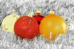 Christmas balls on silver tinsel Stock Images
