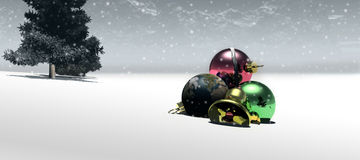 Christmas balls on snow. A wide panoramic view of Christmas balls or baubles on a snowy landscape with a tree in the background Royalty Free Stock Photo