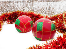 Christmas balls in the snow. Colourful Christmas decorations lying in the snow royalty free stock images
