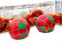 Christmas balls in the snow. Colourful Christmas decorations lying in the snow royalty free stock photos