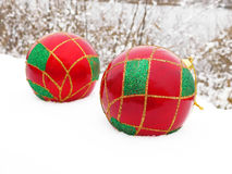 Christmas balls in the snow. Colourful Christmas decorations lying in the snow royalty free stock photography