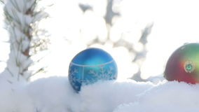 Christmas balls on snow-covered fir branch stock footage