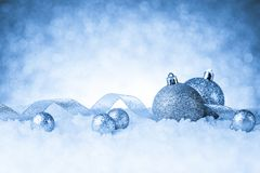 Christmas balls in snow on glitter background Royalty Free Stock Images