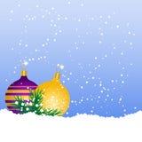 Christmas balls on the snow. Violet and yellow Christmas balls on the snow Stock Photo