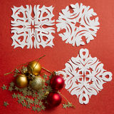 Christmas balls and snowflakes on a red background Stock Images