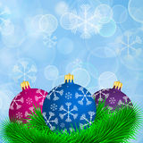 Christmas balls with spruce branches in snowfall. On blue background Royalty Free Stock Photo