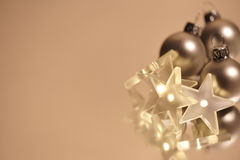 Christmas balls and stars. Christmas balls with in a star shape lights on champagne colored background Royalty Free Stock Images
