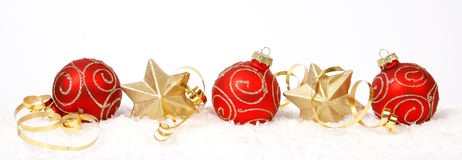 Christmas balls and stars. Red-golden baubles and golden stars on the snow Royalty Free Stock Photos
