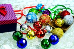 Christmas balls on a table. Assortment of Christmas balls on a table with a present box and some ribbons Royalty Free Stock Photo