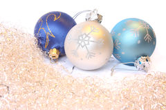 Christmas balls and a tinsel. Three Christmas balls and golden tinsel. Isolated on white Royalty Free Stock Photography