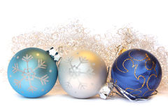 Christmas balls and a tinsel. Three Christmas balls and golden tinsel. Isolated on white Stock Images