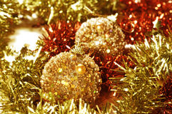 Christmas balls and tinsel. Closeup of some shiny golden christmas balls and golden and orange tinsel Stock Photography