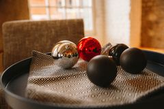 Christmas balls are on a tray against the window stock image