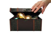 Christmas balls in a treasure chest (+clipping path). Hand of a woman opening a treasure chest filled with Christmas balls. With clipping path royalty free stock photo