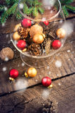 Christmas balls, walnuts, pine cones and snow falling Royalty Free Stock Photos