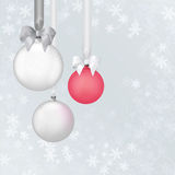 Christmas balls with white ribbon and bows on the snowflake background.  Stock Photos