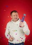 Christmas bang. Joyful man in white knitted sweater holding confetti cracker Stock Images