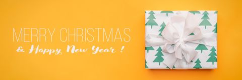 Christmas banner. Beautiful christmas gift isolated on bright yellow background. Turquoise colored wrapped xmas box. royalty free stock photography