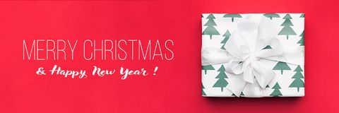 Christmas banner. Beautiful christmas gift isolated on red background. Wrapped xmas box. Gift wrapping. Christmas banner. Beautiful christmas gift isolated on royalty free stock photos