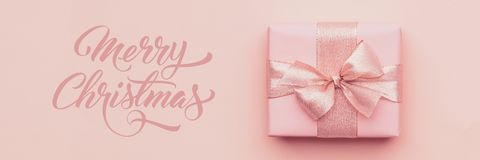Christmas banner. Beautiful pink christmas gift on pastel pink paper background. Christmas banner. Beautiful pink christmas gift isolated on pastel pink paper royalty free stock images