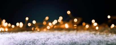 Christmas banner with golden party lights. Christmas panorama banner with golden party lights in a sparkling background bokeh over winter snow with copy space Royalty Free Stock Photos