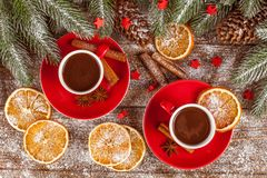 Christmas banner with green tree, cones, red cups with hot chocolate, orange and cinnamon on brown wooden background. Under imitative snow. Xmas and New Year Stock Image