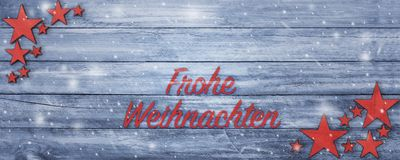 Christmas greeting banner with German text on wood table. Christmas banner in greeting card style with German Frohe Weihnachten Merry Christmas text, ultra large royalty free stock image