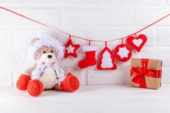 Christmas banner with handmade felt decorations, toy bear in Santa costume, gift box with red ribbon on white wooden background. Stock Photo