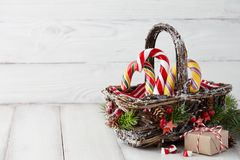 Christmas basket with candy canes on white planks Stock Image