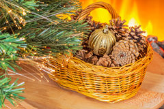 Christmas basket with cones near the fireplace Royalty Free Stock Photo