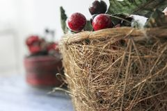 Closeup Christmas basket with cherries and pines. A Christmas basket filled with cherries, pines and green and red decorations Stock Photo