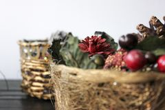 Closeup Christmas basket with cherries and pines. A Christmas basket filled with cherries, pines and green and red decorations Royalty Free Stock Images